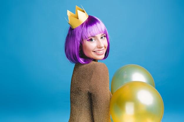 Positive helle gefühle der freudigen jungen frau mit geschnittenem lila haar feiern party mit luftballons. goldene krone, fröhliche stimmung, feiertagsfeier, geburtstag. Kostenlose Fotos