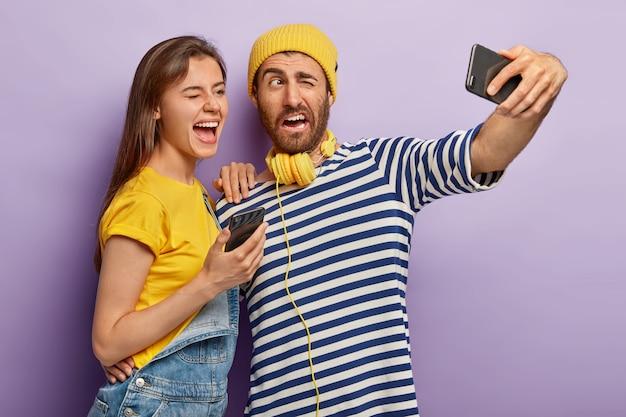 Positive kerl und frau blinzeln augen, posieren vor handykamera, machen foto für internet-blog, machen selfie, haben fröhliche ausdrücke Kostenlose Fotos