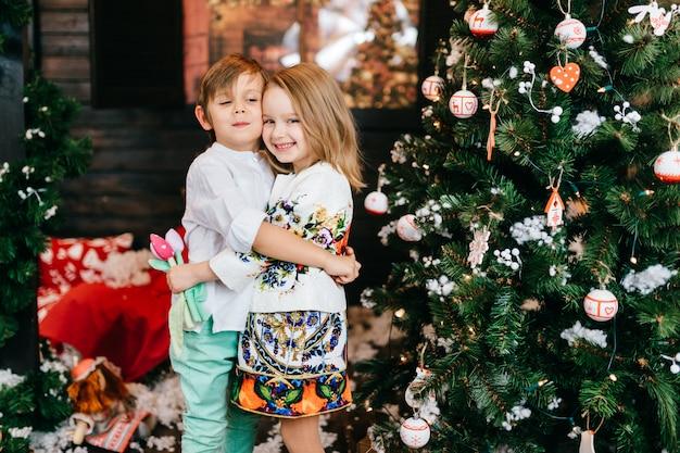 Positive kinder, die im studio mit cristmas baum und dekorationen des neuen jahres umarmen und lächeln. Premium Fotos