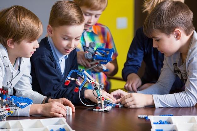 Positive kinder spielen und montieren den konstrukteur im kinderzimmer. Premium Fotos