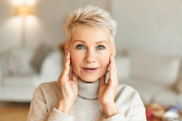 Positive menschliche gesichtsausdrücke, gefühle, emotionen und reaktionen. bild der emotionalen attraktiven reifen frau mit blonden haaren und blauen augen, die hände auf gesicht halten und mit etwas erstaunt sind Kostenlose Fotos