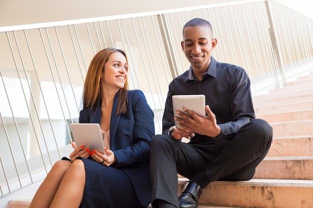 Positive mitarbeiter, die tabletten halten und auf treppe sitzen Kostenlose Fotos
