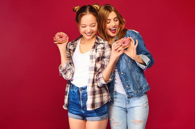 Positive modelle halten frische rosa donuts mit pulver bereit, um süßigkeiten zu genießen Kostenlose Fotos