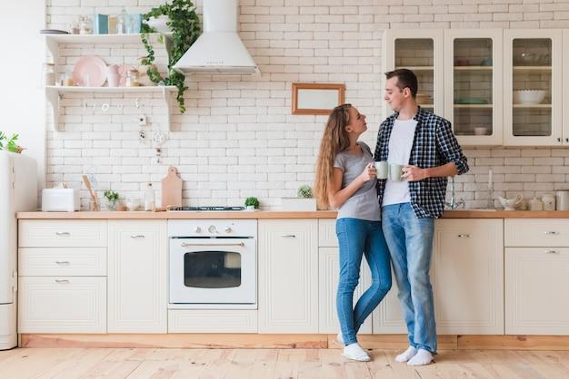 Positive paare, die in der küche stehen und tee genießen Kostenlose Fotos