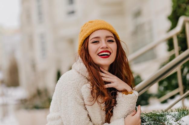 Positive rothaarige frau, die über verschwommene natur lacht. raffiniertes ingwermädchen, das während des winterfotoshootings lächelt. Kostenlose Fotos