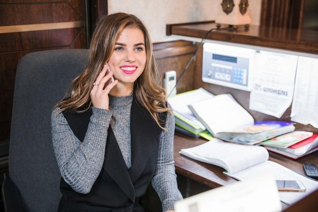 Positive überzeugte attraktive junge empfangsdame, die bei tisch sitzt, am handy spricht Kostenlose Fotos