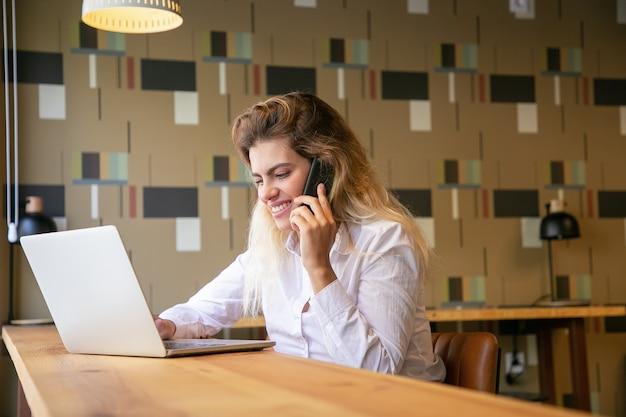 Positive unternehmerin, die am laptop arbeitet und auf handy im gemeinsamen arbeitsraum spricht Kostenlose Fotos