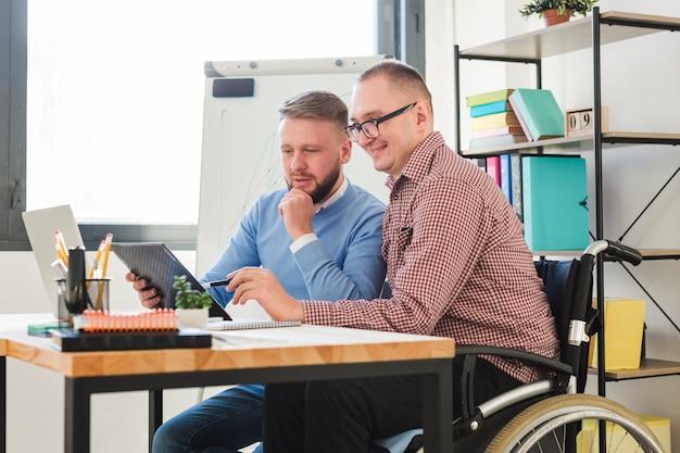 Positiver behinderter arbeiter zusammen mit dem manager im büro Kostenlose Fotos