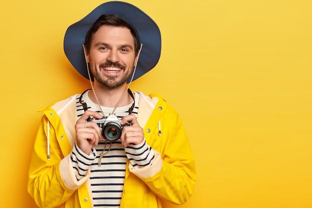Positiver gutaussehender mann hält retro-kamera, lächelt angenehm, in aktiver kleidung gekleidet, posiert vor gelbem hintergrund. Kostenlose Fotos