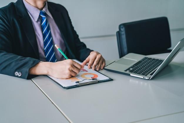 Positiver junger geschäftsmann, der mit dokumenten und laptop sitzt und arbeitet, Premium Fotos