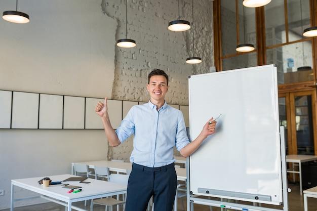 Positiver junger hübscher lächelnder mann, der an leerer weißer tafel mit markierung steht, Kostenlose Fotos