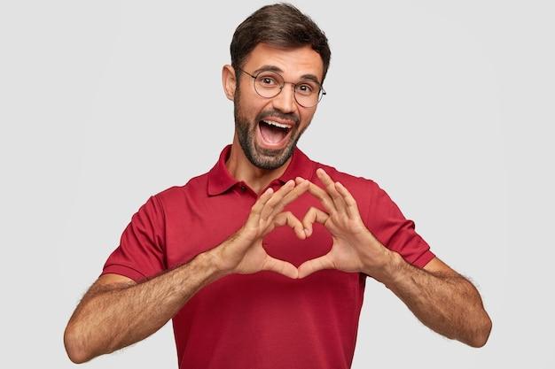 Positiver kaukasischer mann mit fröhlichem ausdruck, zeigt herzgeste über brust, drückt freundliche haltung und liebe aus, trägt rotes helles t-shirt, isoliert über weißer wand Kostenlose Fotos