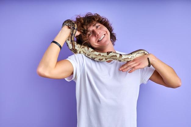 Positiver mann, der schlange in händen hält, keine angst, keine phobie. kaukasischer mann im weißen t-shirt, das mit schlange aufwirft Premium Fotos