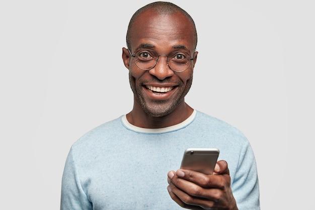 Positiver mann mit breitem lächeln, hält modernes handy, tippt sms und feedback, surft in sozialen netzwerken Kostenlose Fotos