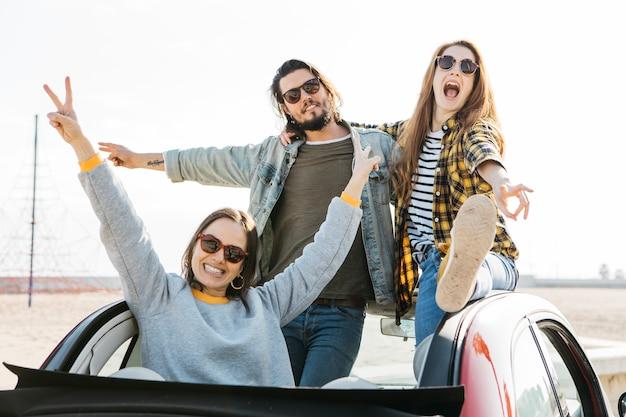 Positiver mann und weinende frauen, die spaß haben und sich heraus vom auto lehnen Kostenlose Fotos