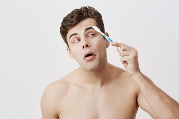 Positiver nackter muskulöser typ mit trendiger frisur, gesunder haut, gesichtern, konzentrierte sich darauf, seine augenbrauen mit zahnbürste zu kämmen. attraktives gut aussehendes männliches posieren. Kostenlose Fotos