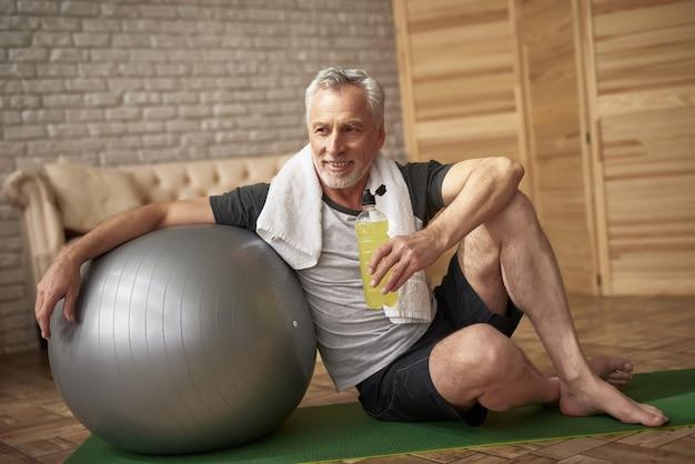 Positiver pensionär trinkt wasser nach training. Premium Fotos