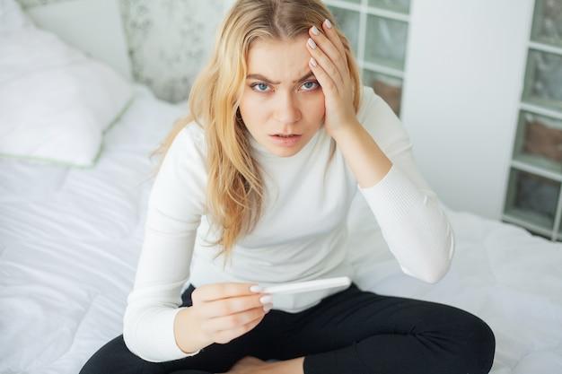 Positiver schwangerschaftstest, junge frau, die nach schwangerschaftstestergebnis zu hause betrachten deprimiert und traurig sich fühlt Premium Fotos