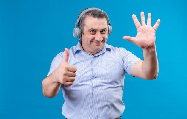 Positiver und freudiger mann mittleren alters im blau gestreiften hemd, das kopfhörer trägt, die mit den fingern nummer sechs auf einem blauen hintergrund zeigen Kostenlose Fotos