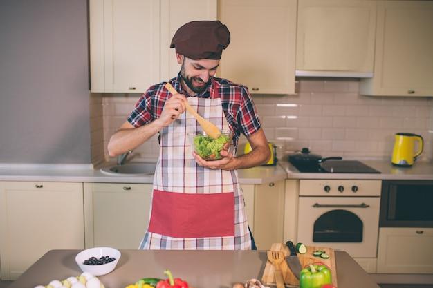 Positiver und glücklicher koch steht in der küche und hält glasschüssel mit salat. er mischte es mit einem holzlöffel. junger mann schaut auf es herab. Premium Fotos