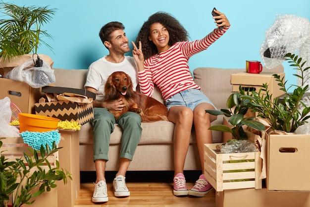 Positives ehepaar auf sofa mit hund, umgeben von pappkartons Kostenlose Fotos
