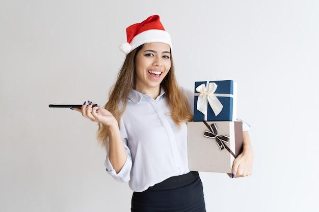 Positives mädchen, das mit weihnachtsgeschenken aufwirft Kostenlose Fotos