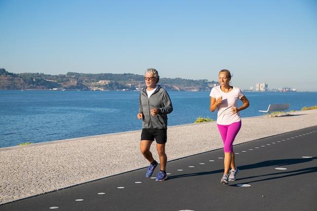 Positives reifes paar, das aktiven lebensstil beibehält und am flussufer am morgen joggt. aktivitätskonzept für rentner Kostenlose Fotos