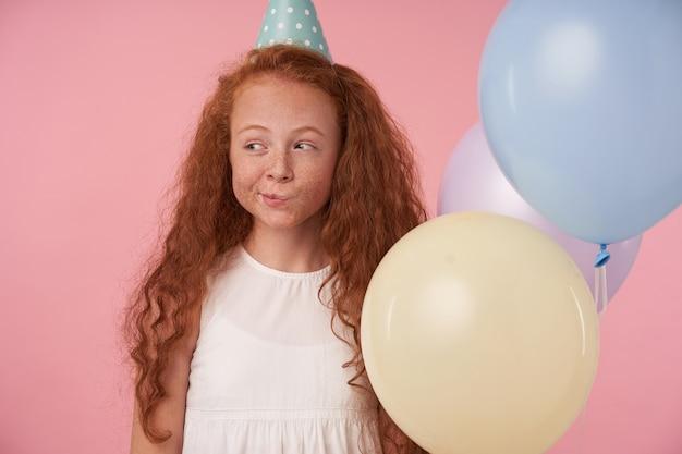 Positives weibliches kind mit rotem lockigem haar in festlichen kleidern und geburtstagskappe steht vor rosa hintergrund, lächelt fröhlich und schaut zur seite über farbige ballons. kinder- und feierkonzept Kostenlose Fotos