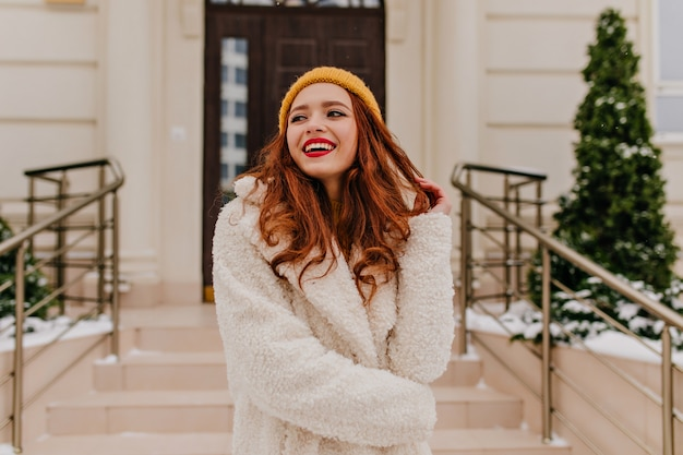 Positives weibliches modell, das im wintertag lacht. blithesome ingwermädchen, das mit glück lächelt. Kostenlose Fotos
