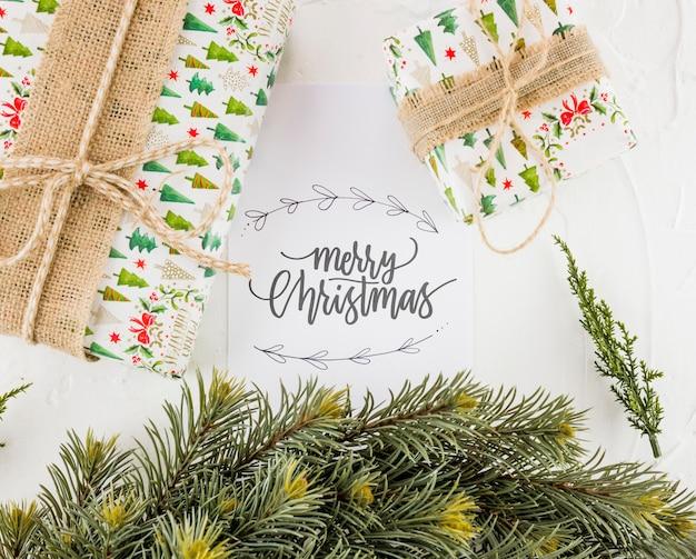 Postkarte mit aufschrift der frohen weihnachten nahe präsentkartons und den tannenzweigen Kostenlose Fotos