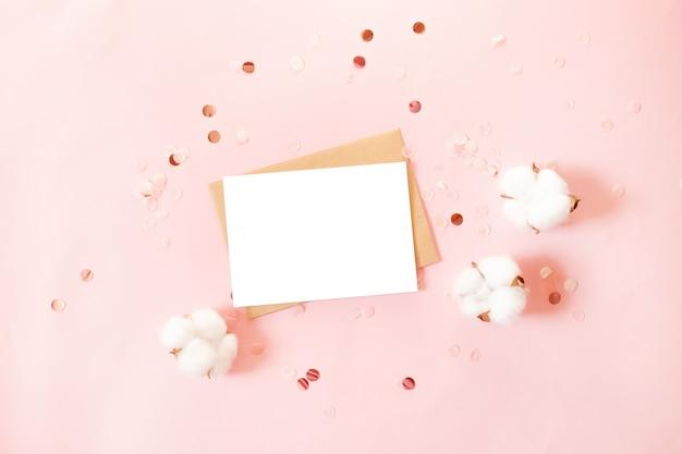 Postkarte mit kraftpapierumschlag, glitzerdekor und baumwollblumen auf rosa hintergrund Premium Fotos