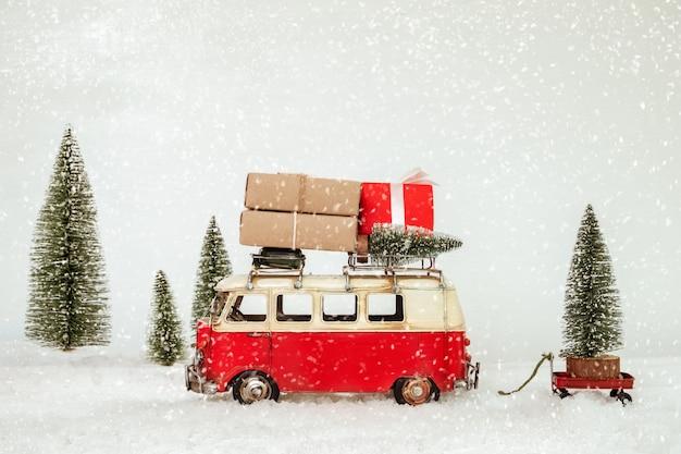 Postkartenhintergrund der frohen weihnachten - tragende geschenke des antiken miniaturautos (geschenkbox) auf dach und weihnachtsbaum im wald des verschneiten winters. Premium Fotos