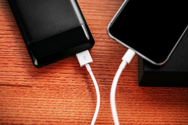 Powerbank lädt den smartphone auf, der auf holz lokalisiert wird Premium Fotos