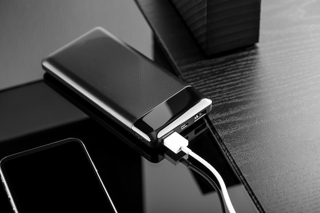 Powerbank lädt den smartphone auf, der auf schwarzem hintergrund lokalisiert wird Premium Fotos
