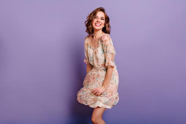 Prächtiges mädchen mit hellbraunem lockigem haar, das mit lächeln im lila studio tanzt Kostenlose Fotos
