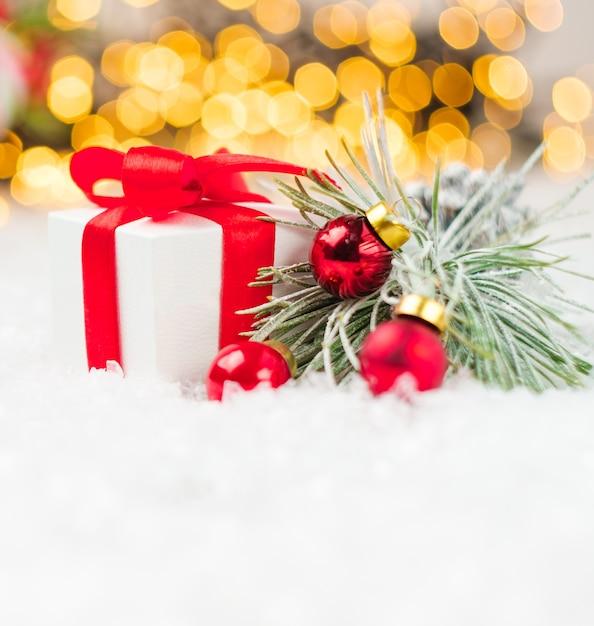 Präsentieren sie box mit roten bändern rote kugeln auf dem schnee auf dem hintergrund des unscharfen weihnachtsbaums Premium Fotos
