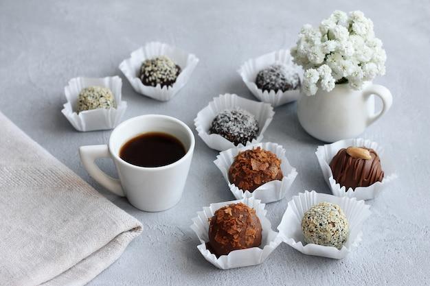 Pralinen, ein tasse kaffee und ein blumenstrauß für valentinstag auf grauer tabelle. Premium Fotos