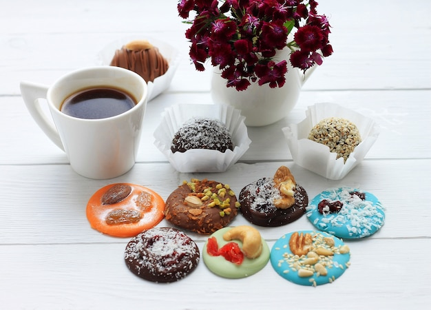Pralinen, eine tasse kaffee und ein blumenstrauß zum valentinstag auf holz Premium Fotos