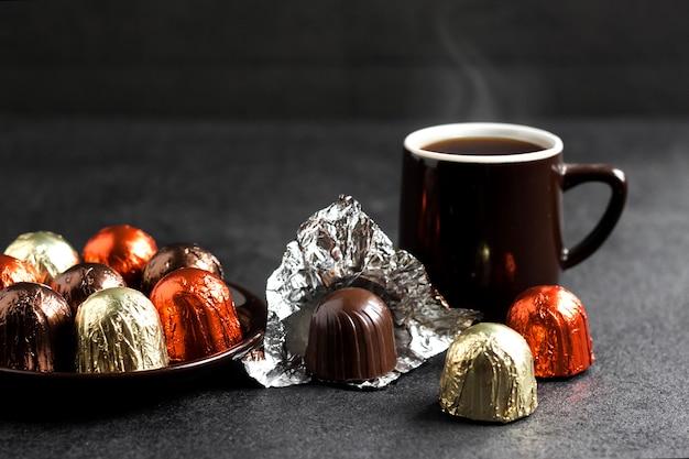 Pralinen in mehrfarbiger folie und zwei tassen kaffee eingewickelt Premium Fotos