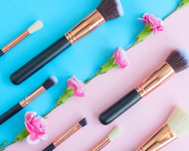 Premium make-up pinsel, lidschatten-palette und blumen auf einem farbigen blauen und rosa hintergrund, kreative kosmetik flach lag mit diagonaler zusammensetzung Premium Fotos