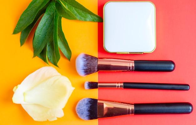 Premium make-up pinsel und rouge auf einem farbigen roten und orangefarbenen hintergrund, kreative kosmetik flach legen, kopierraum Premium Fotos
