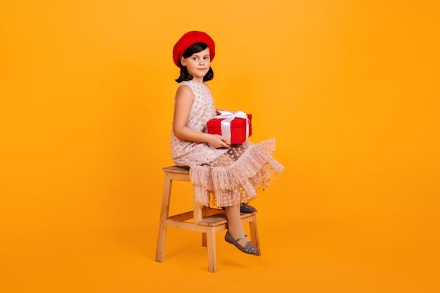 Preteen mädchen im kleid hält geburtstagsgeschenk. kind mit geschenk sitzt auf stuhl auf gelber wand. Kostenlose Fotos