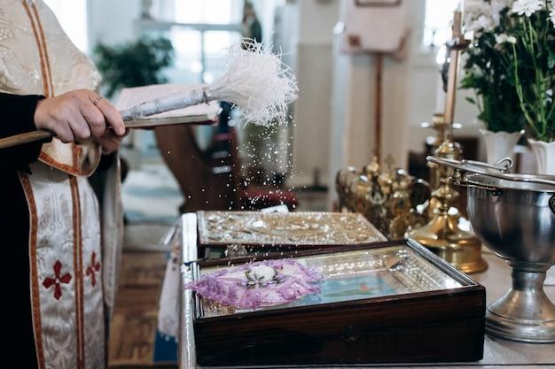 Priester besprüht eheringe in der kirche mit weihwasser Kostenlose Fotos