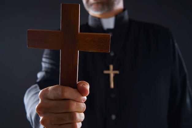 Priester, der kreuz des hölzernen betens hält Premium Fotos