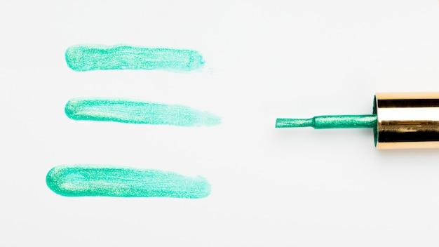 Probe des grünen nagellackanschlags nahe bürste über hintergrund Kostenlose Fotos
