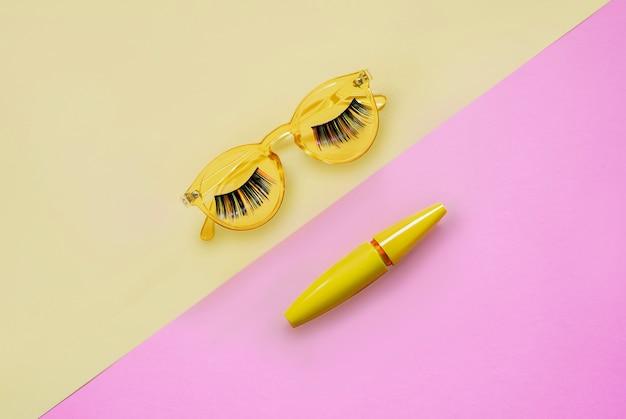 Produkt für augen make-up. wimperntusche in gelber tube auf rosafarbener und gelber sonnenbrille mit langfarbigen haarwimpern Premium Fotos