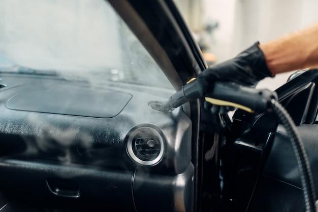 Professionelle chemische reinigung des autoluftkanals mit dampfreiniger. autowaschdienst, hygiene im fahrzeugsalon, männlicher arbeiter entfernt schmutz und staub Premium Fotos