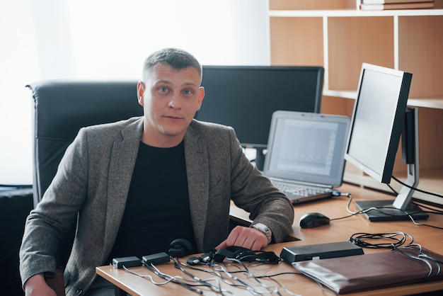 Professionelle dienstleistungen. der polygraph-prüfer arbeitet im büro mit der ausrüstung seines lügendetektors Kostenlose Fotos