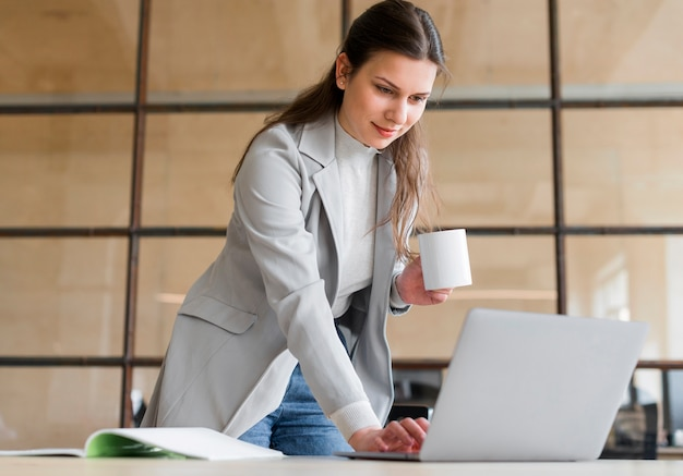 Professionelle junge lächelnde geschäftsfrau, welche das kaffeetasseweiß arbeitet an laptop hält Kostenlose Fotos