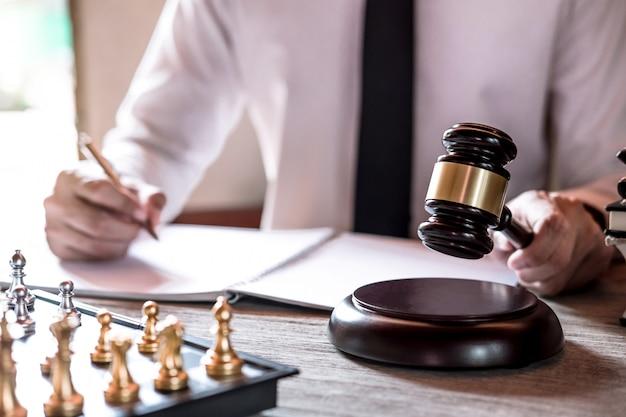 Professionelle männliche rechtsanwälte, die an dem gerichtssaal arbeiten, der am tisch sitzt und papiere mit hammer unterzeichnet Premium Fotos
